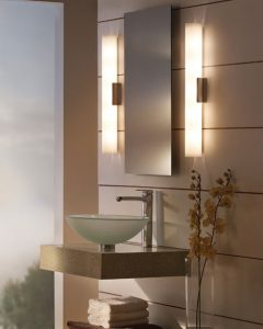 Modern bathroom sink with long lighting fixtures on each side of mirror.